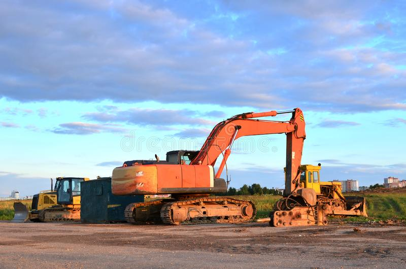 Large tracked excavator and bulldozers on a construction site, background of the sunset. royalty free stock image