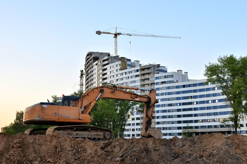 Large tracked excavator digs the ground for the foundation and construction of a new building in the city. royalty free stock photos