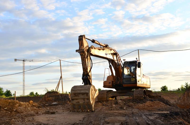Large tracked excavator digs the ground for the foundation and construction of a new building in the city. royalty free stock photo
