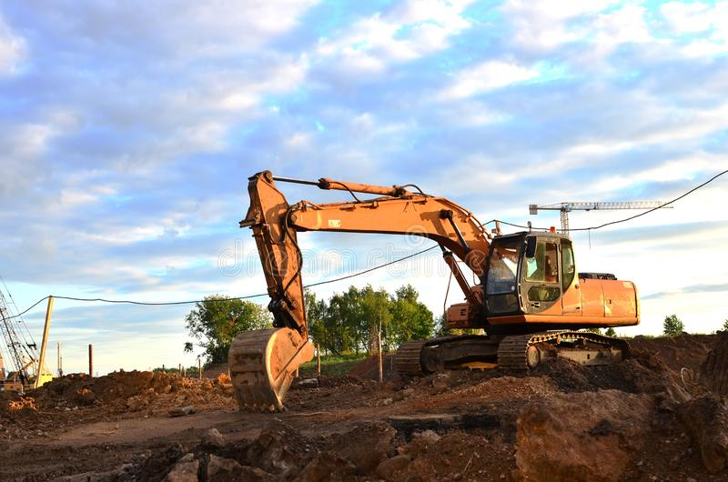 Large tracked excavator digs the ground for the foundation and construction of a new building in the city. stock image
