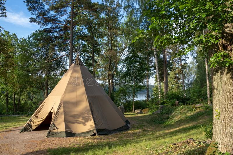 A large traditional teepee tent with luxurious glamping interior provides alternate but comfortable lodging for outdoor adventurer royalty free stock photography