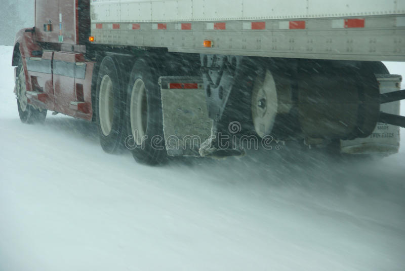 Large trucks fight a winter storm stock photos