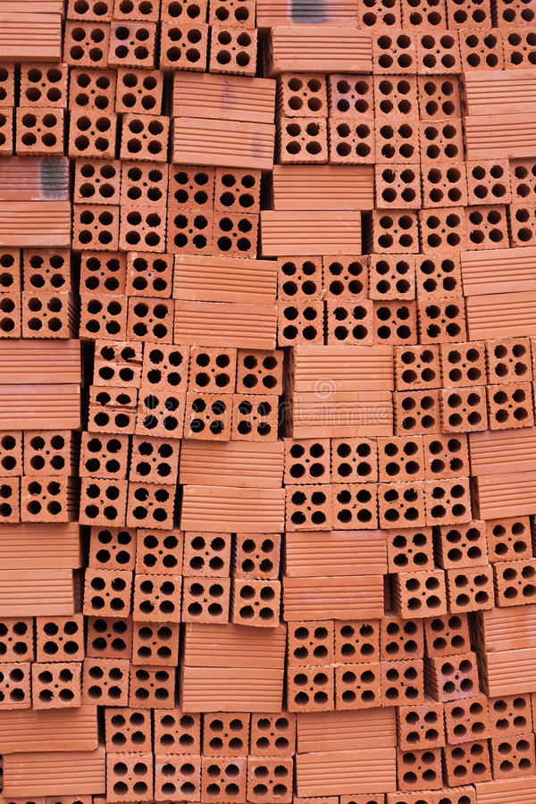 Large vertical uneven flow of red bricks. For construction. Textural background royalty free stock images