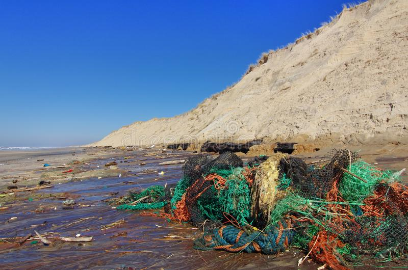 Beach pollution with plastics and fishing nets stock photos