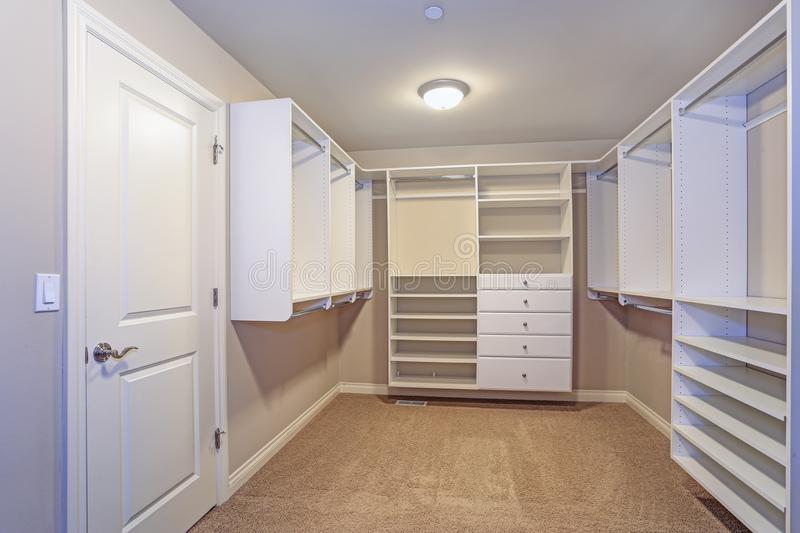 Large walk-in closet with white shelves, drawers royalty free stock images