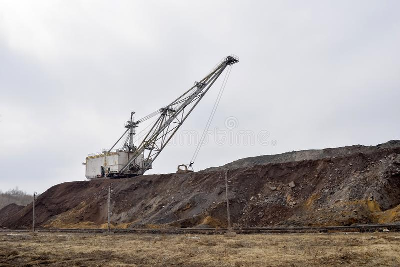 Large walking excavator in anticipation of rolling stock transporting overburden for storage in dumps. Industrial landscape after the destruction of nature by stock photography