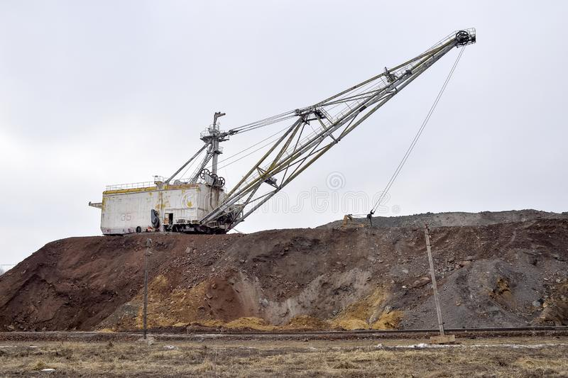 Large walking excavator in anticipation of rolling stock transporting overburden for storage in dumps. Industrial landscape after the destruction of nature by royalty free stock images