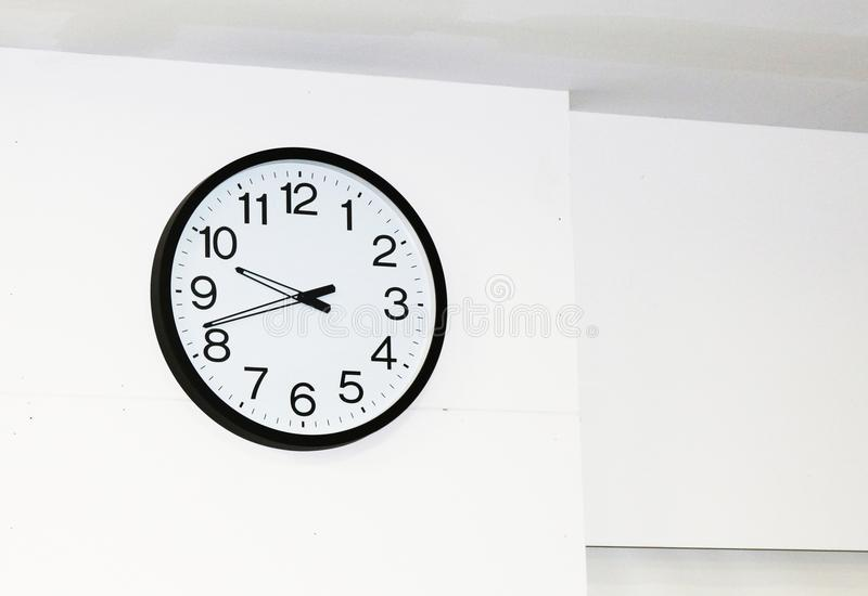 Large wall clock with white face and black border. Large wall clock with white face, black border, stylish black hands and clear black numerals on a white wall royalty free stock photos