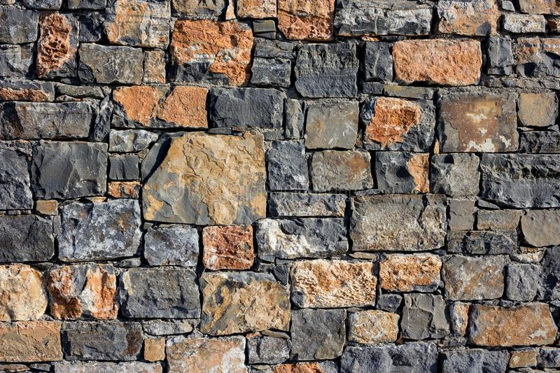 Large wall of natural granite stones of different size and color, gray texture on a summer day, multi-colored granite royalty free stock images