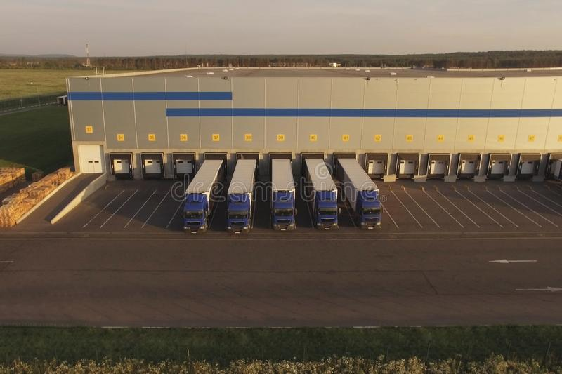 Large warehouse complex with parked trucks awaiting loading. Logistics center, warehouse terminal stock images
