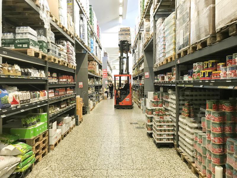Large warehouse wholesale with rows of aisles and shelves from floor to ceiling. Forklift lifting boxes to the upper shelves. stock photo