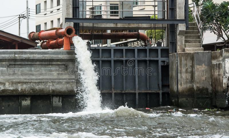 Large water pipe discharging liquid waste into river royalty free stock images