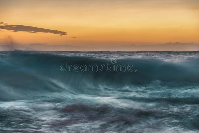Large wave cresting and breaking at sunset stock photography
