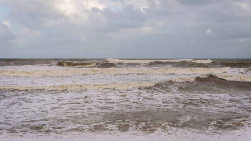Large waves hit Batu Buruk Beach in Kuala Terengganu during monsoon season. Strong wind from ocean hit hard the coastline. Dark and cloudy cloud background royalty free stock image