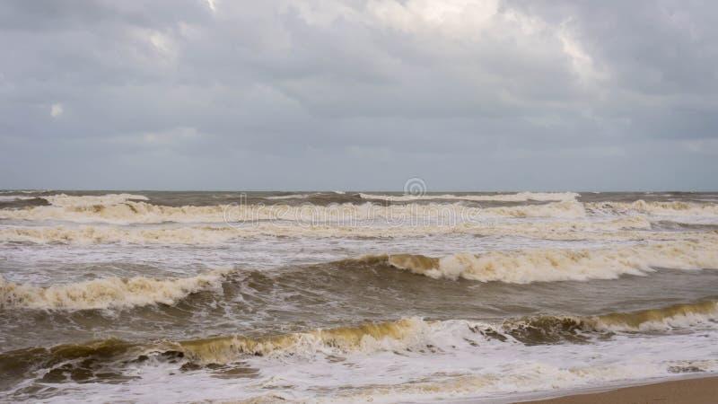 Large waves hit Batu Buruk Beach in Kuala Terengganu during monsoon season. Strong wind from ocean hit hard the coastline. Dark and cloudy cloud background royalty free stock photos