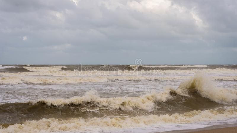 Large waves hit Batu Buruk Beach in Kuala Terengganu during monsoon season. Strong wind from ocean hit hard the coastline. Dark and cloudy cloud background stock photography