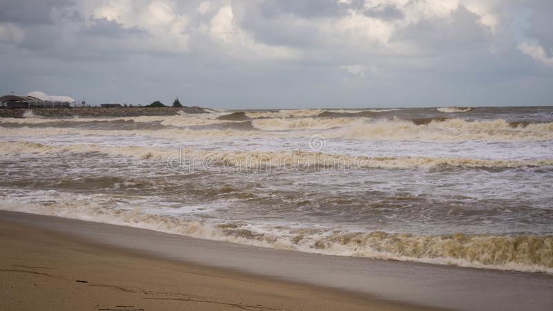 Large waves hit Batu Buruk Beach in Kuala Terengganu during monsoon season. Strong wind from ocean hit hard the coastline. Dark and cloudy cloud background stock images