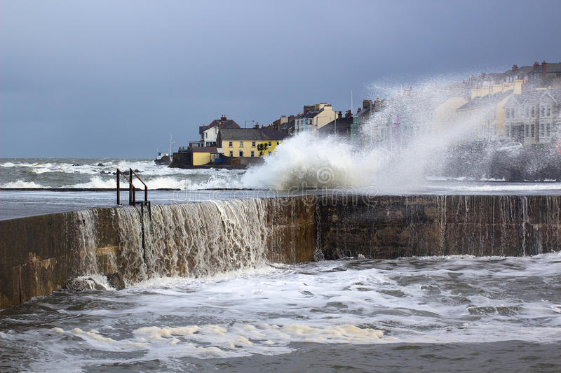 Large waves from the Irish Sea during a winter storm batter the harbor wall at the long Hole in Bangor Ireland. The Long Hole harbor wall in Bangor Ireland is stock images