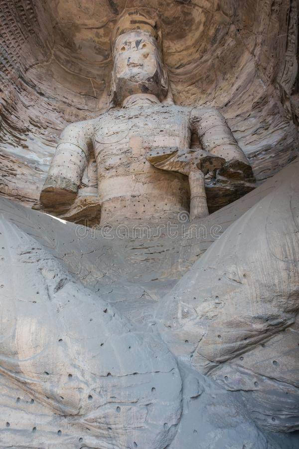 Large weatherworn Buddha statue in cave 17 of the Yungang Grottoes royalty free stock photography