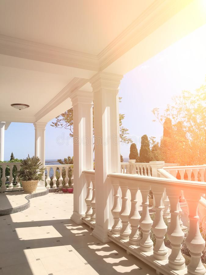 Large white balcony with columns and views of the Park and the sea on a Sunny day royalty free stock photos