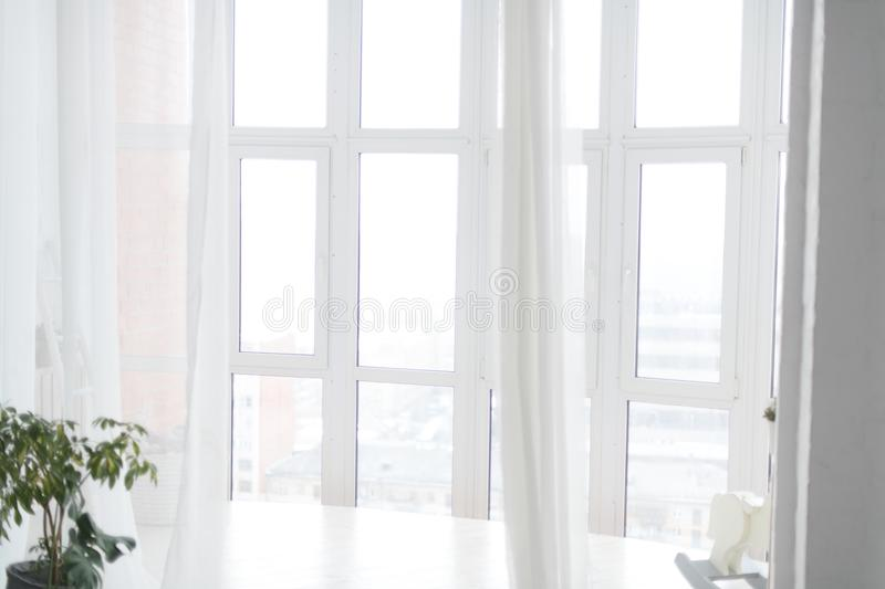 Large white bright Windows with transparent curtains. Horizontal royalty free stock image
