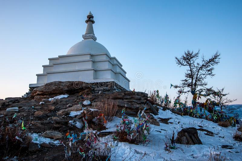 A large white Buddhist stupa against a blue sky and many colorful ribbons on bushes on the sacred island of Ogoy on Lake Baikal. stock photography