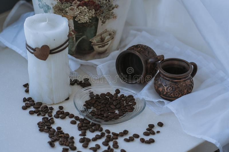 a large white candle stands on the window in the morning with flowers and a white background with coffee beans scattered near royalty free stock photo