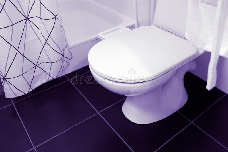 Large white and ceramic toilet seat fixture. Shower, curtain. White Bathrobe on a hanger stock photo