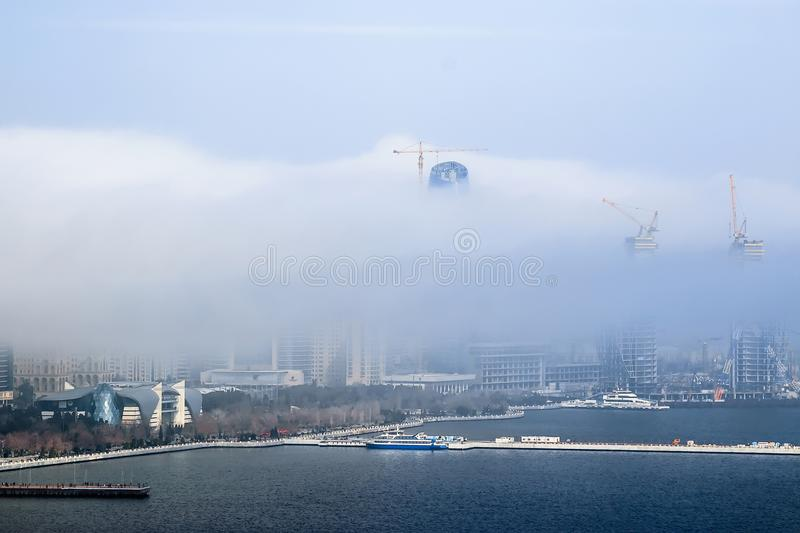 A large white cloud fell on the city and closed the view of the building. Foggy cloud moves from the sea to the city. stock images