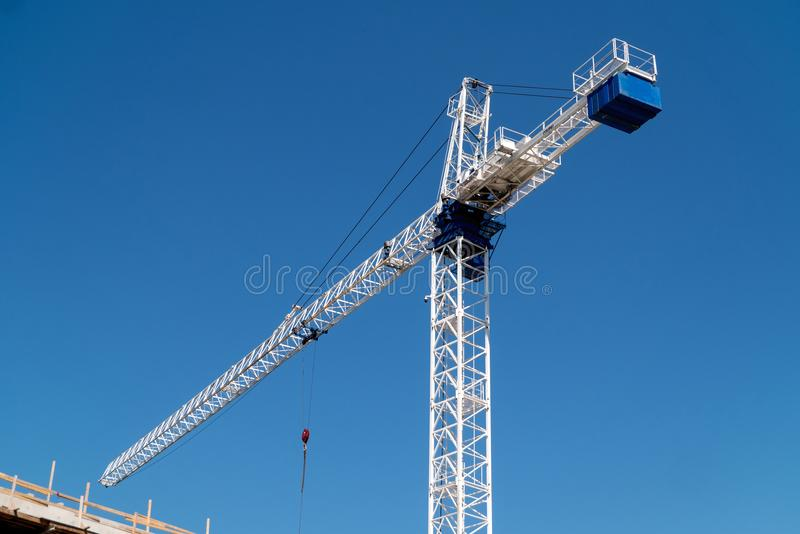 Large white construction crane is contrasted against a deep blue sky. New building under construction as a large white metal crane hovers above the development royalty free stock photo