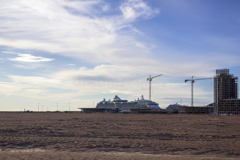Large white cruise liner in the sandy desert near the tower cranes building modern high-rise buildings. A large white cruise liner in the sandy desert near the royalty free stock photos