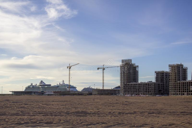Large white cruise liners in the sandy desert near the tower cranes building modern high-rise buildings. A large white cruise liners in the sandy desert near the royalty free stock photo
