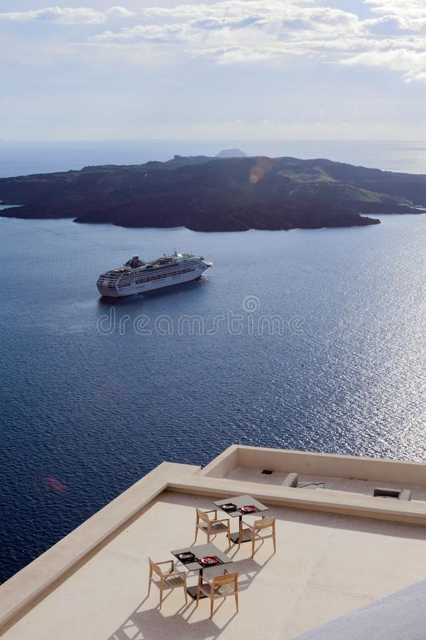 Large white passenger cruise ship in the old port of the Greek city of Fira. Sunset. Travel. Cruises. Santorini, Greece, April 2019. A cozy restaurant, a terrace royalty free stock image