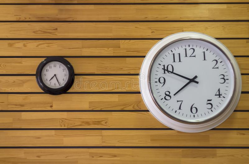 Large white round clock close up and a black small clock with arrows on the yellow wall of wooden planks. horizontal lines. stock photography
