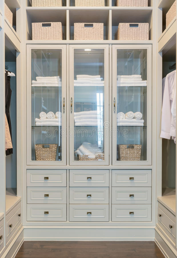 Large white walk-in closet with shelves at home stock photo