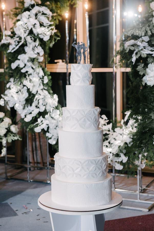 Large white wedding cake with castle shaped towers. Close up celebration cream decoration party big table food beautiful traditional holiday background tasty royalty free stock image