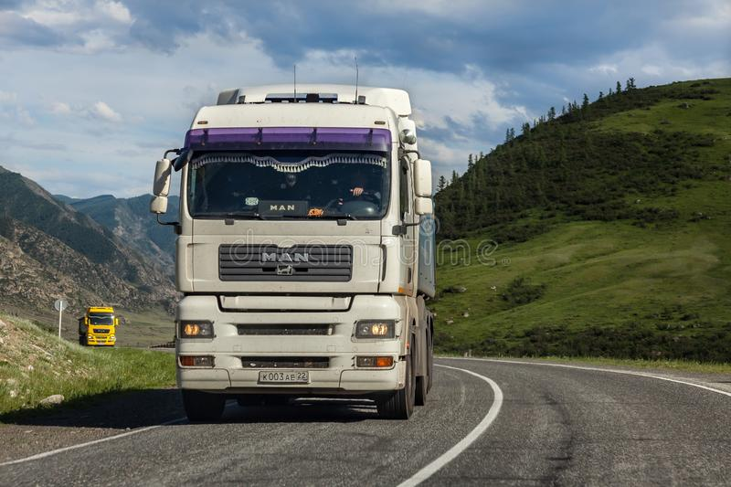 A large white and yellow truck Man rides on a highway in the mountains while transporting goods over long distances. Fast delivery stock image