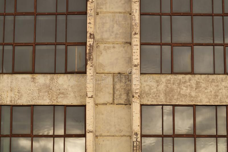 Large windows of the factory on the cement wall. Big windows of the factory on the cement wall background, exterior, house, modern, white, front, apartment stock images