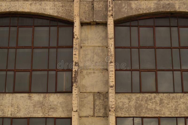 Large windows of the factory on the cement wall. Big windows of the factory on the cement wall background, exterior, house, modern, white, front, apartment royalty free stock images