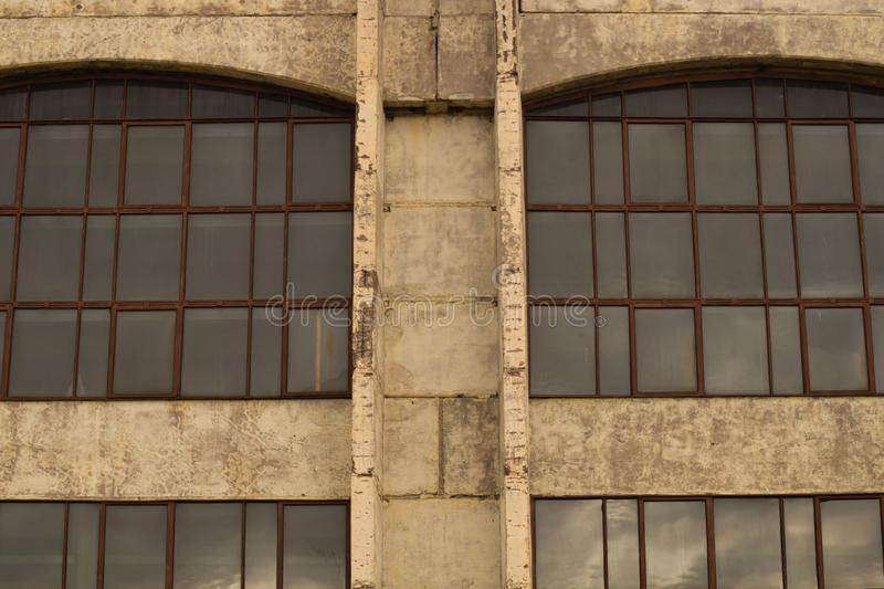 Large windows of the factory on the cement wall. Big windows of the factory on the cement wall background, exterior, house, modern, white, front, apartment royalty free stock photo