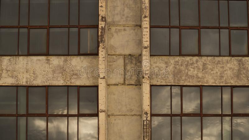 Large windows of the factory on the cement wall. Big windows of the factory on the cement wall background, exterior, house, modern, white, front, apartment stock image
