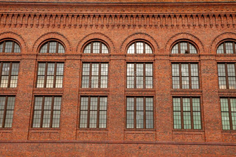 Large windows on the side of a red bricked building royalty free stock image