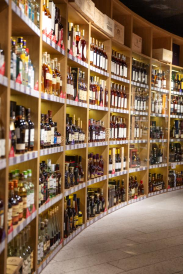 Large wine racks. Many different alcoholic beverages. Luxury enoteca. The photo is blurry. Vertical royalty free stock photography