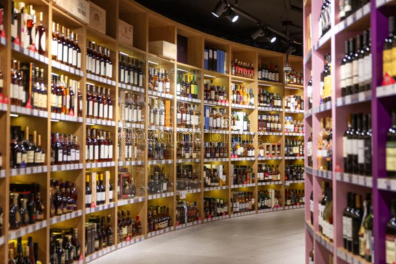 Large wine racks. Many different alcoholic beverages. Luxury enoteca. The photo is blurry. Horizontal stock photography