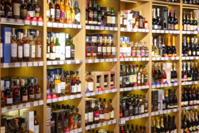 Large wine racks. Many different alcoholic beverages. Luxury enoteca. The photo is blurry. Horizontal stock photo