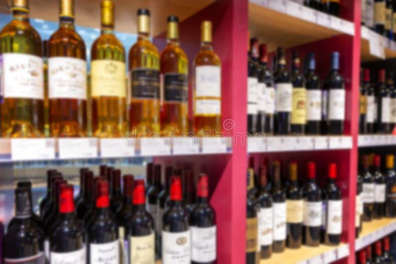 Large wine racks. Many different alcoholic beverages. Luxury enoteca. The photo is blurry. Horizontal royalty free stock image