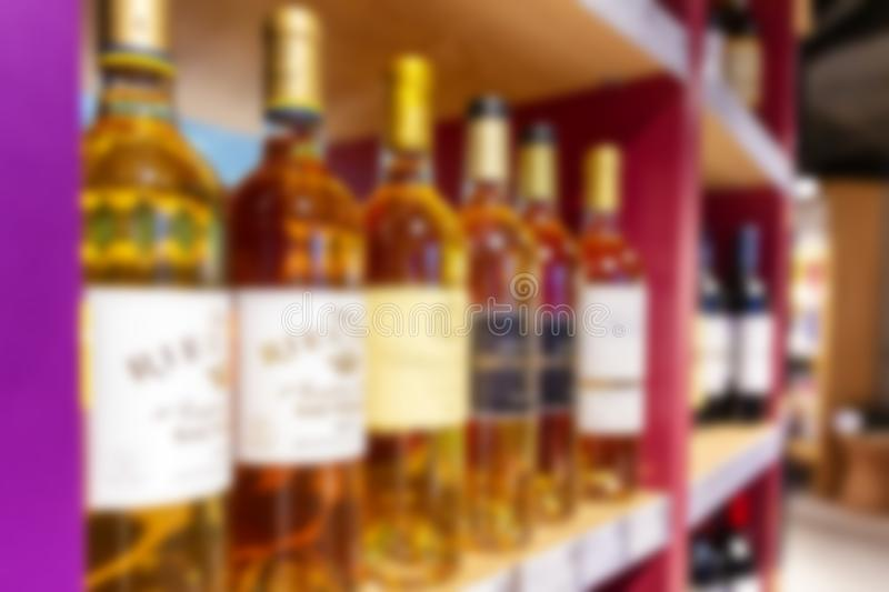 Large wine racks. Many different alcoholic beverages. Luxury enoteca. The photo is blurry. Horizontal royalty free stock photos