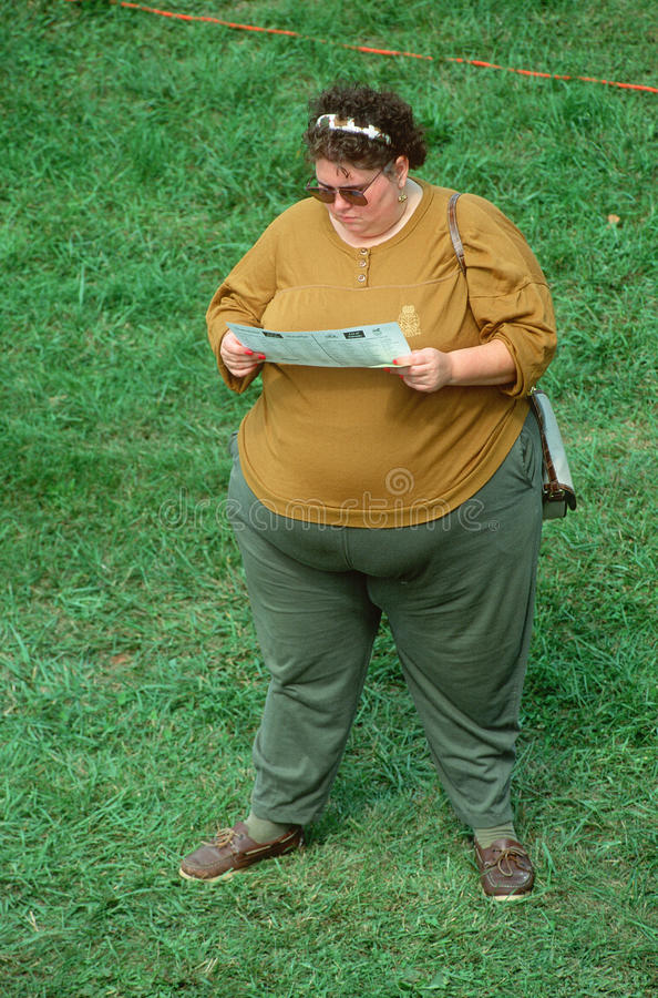 A large woman reading a pamphlet royalty free stock images