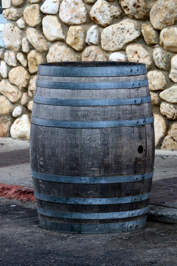 A large wooden barrel stands on a city street. In northern Israel royalty free stock photo