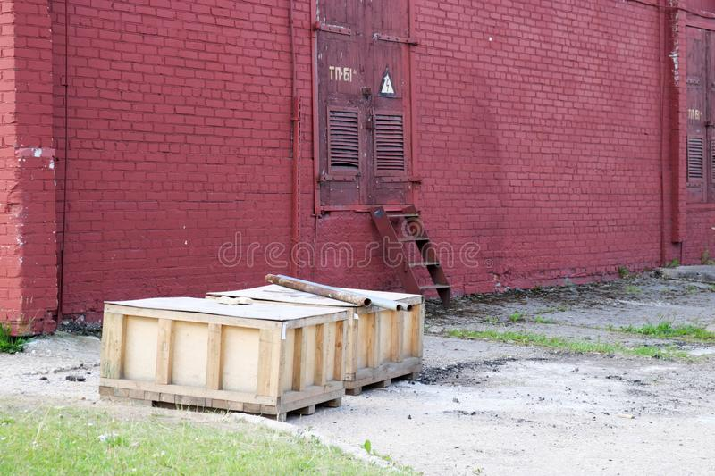 Large wooden boxes with goods stand outside in the open air in the warehouse of an industrial enterprise against a red brick wall stock photography